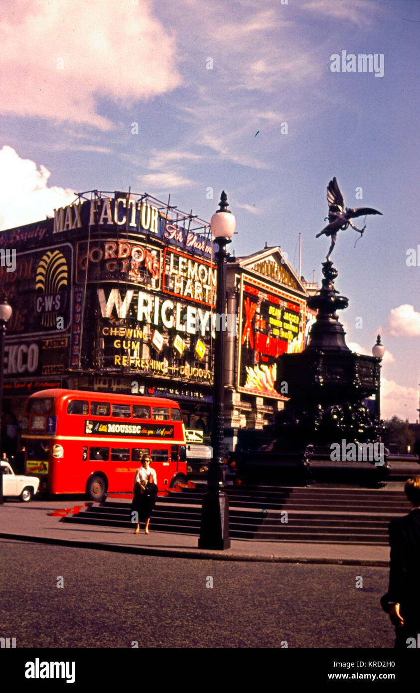 View of Piccadilly Circus, London, in daytime, with a red double-decker bus, advertising for Max Factor, Wrigleys, - Stock Image