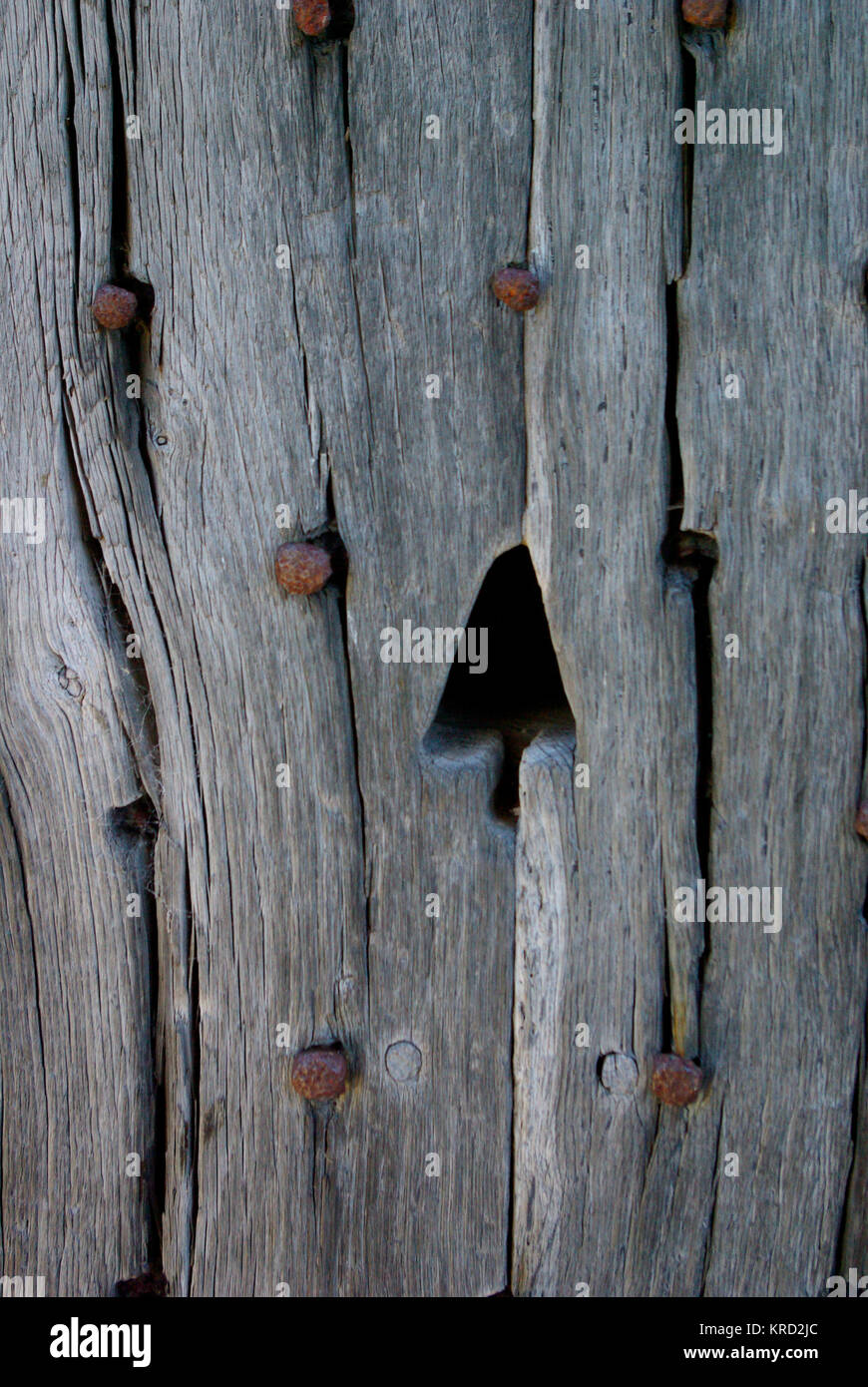 Detailed Close Up Of Wood With Iron Nails And An Arrow Shaped Hole
