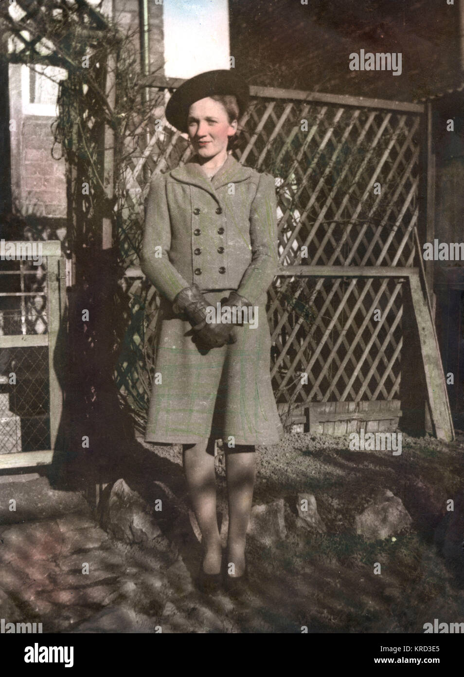A woman, Dorothy Margaret Hunt (born 1924), poses by a trellis and arch in a garden wearing a typical 1940s skirt - Stock Image
