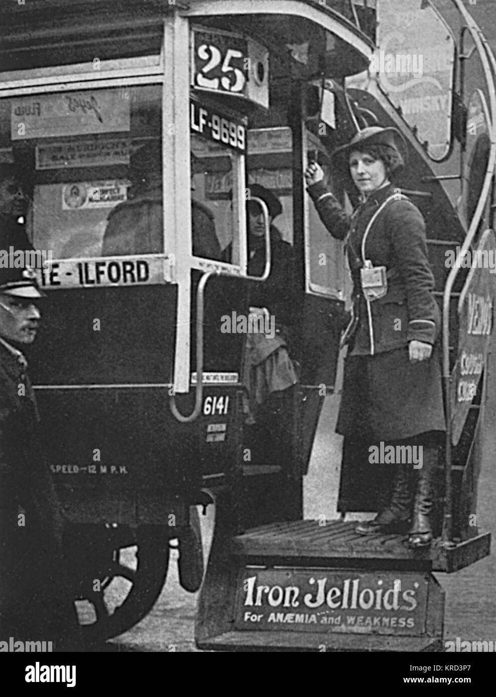 A girl bus conductor in her blue uniform, with gaiters and turned up hat, rings the bell on the no 25 route which - Stock Image