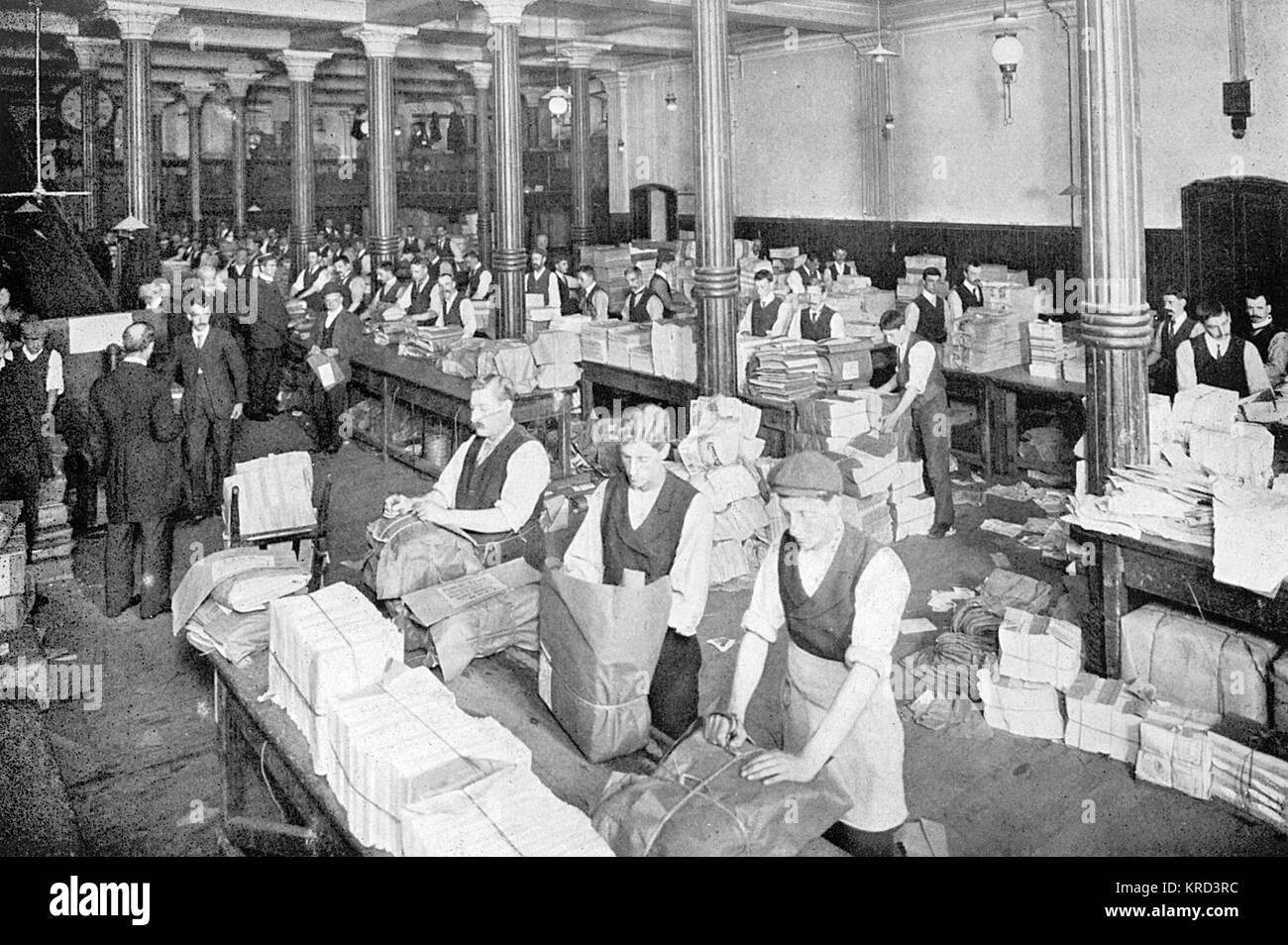 Men working at long tables at W. H. Smith sorting and packing newspapers for distribution by rail throughout the - Stock Image