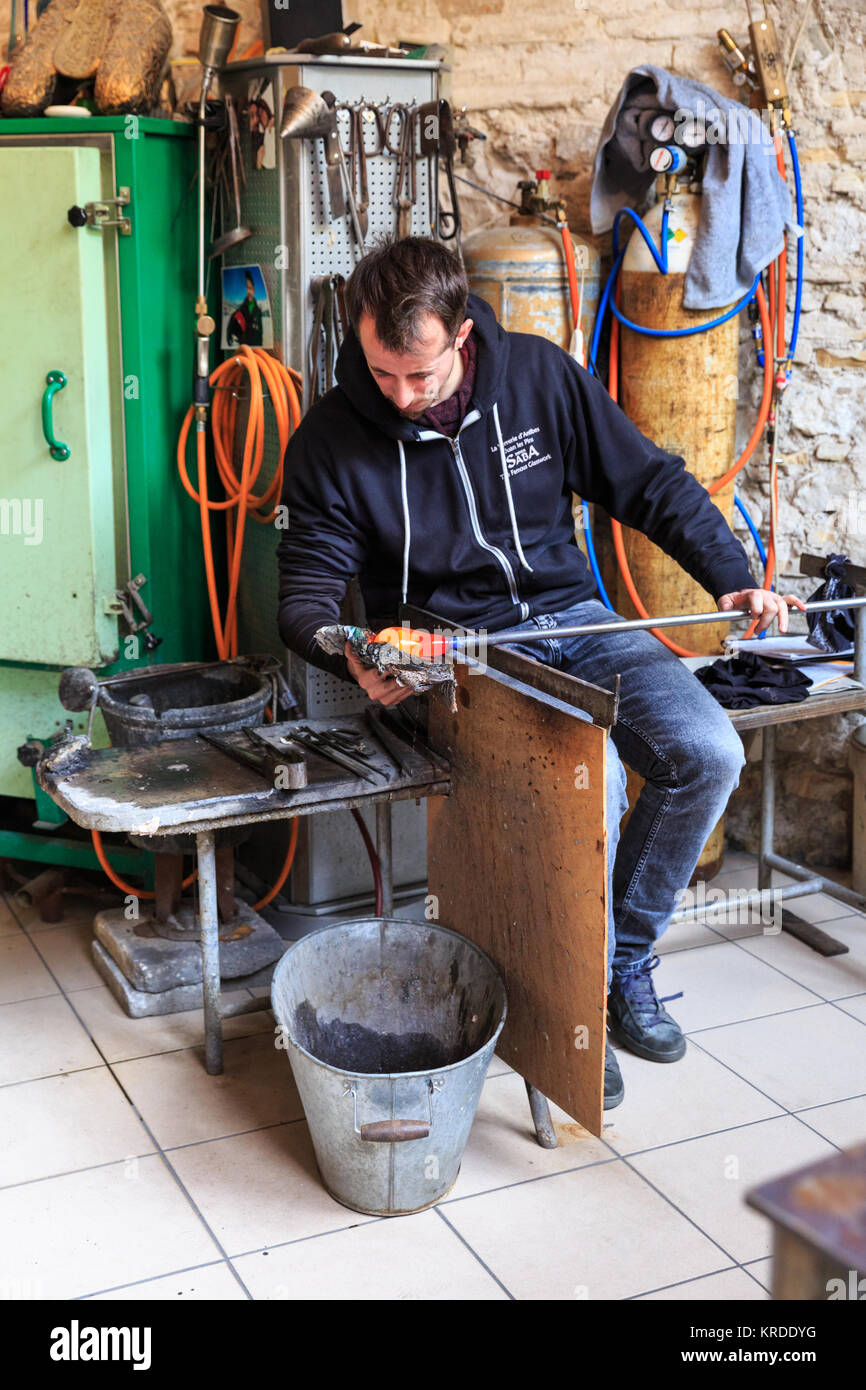 Glass blower at Didier Saba glass blowing studio, moulding a shape in Antibes, French Riviera, France - Stock Image
