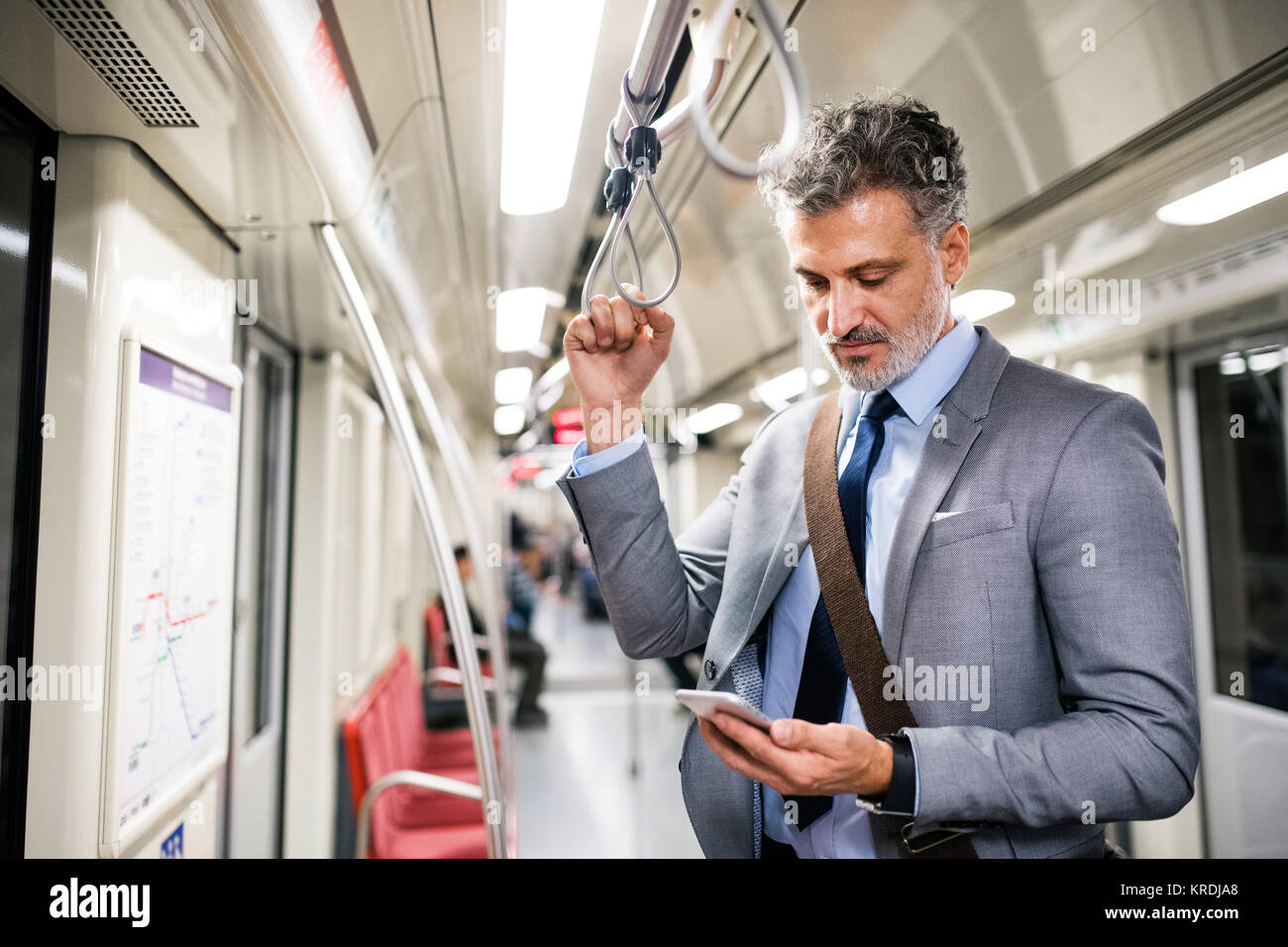 Mature businessman with smartphone in a metro train. Stock Photo