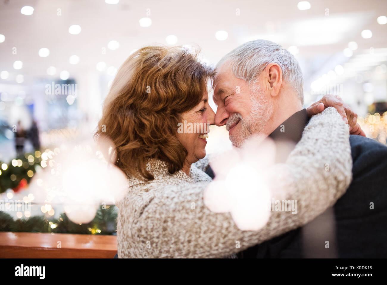 Senior couple doing Christmas shopping, hugging. - Stock Image