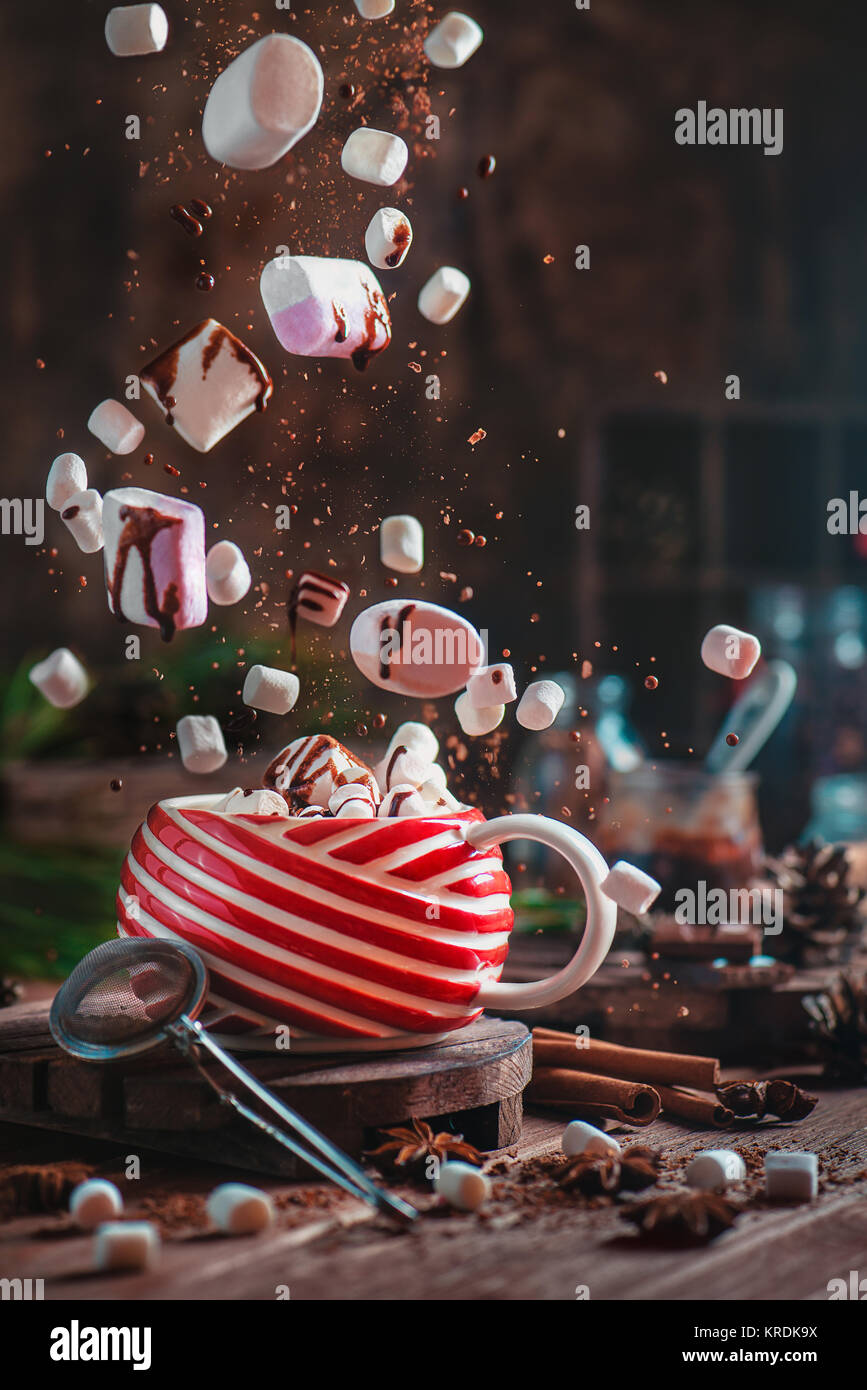 Christmas hot cocoa with flying marshmallows and chocolate. New Year celebration scene with chocolate crumbs, spices - Stock Image