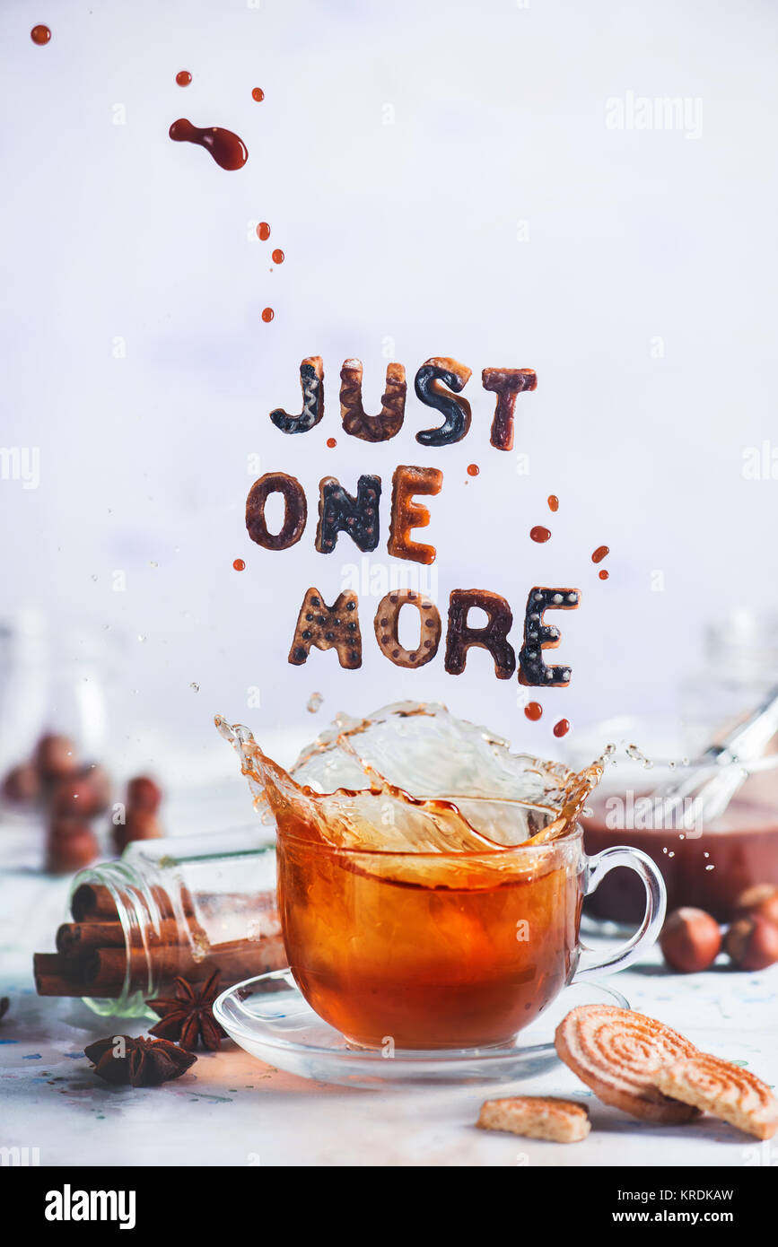 Tea cup with a dynamic splash and glazed cookies forming text Just One More on a light background. Food typography - Stock Image