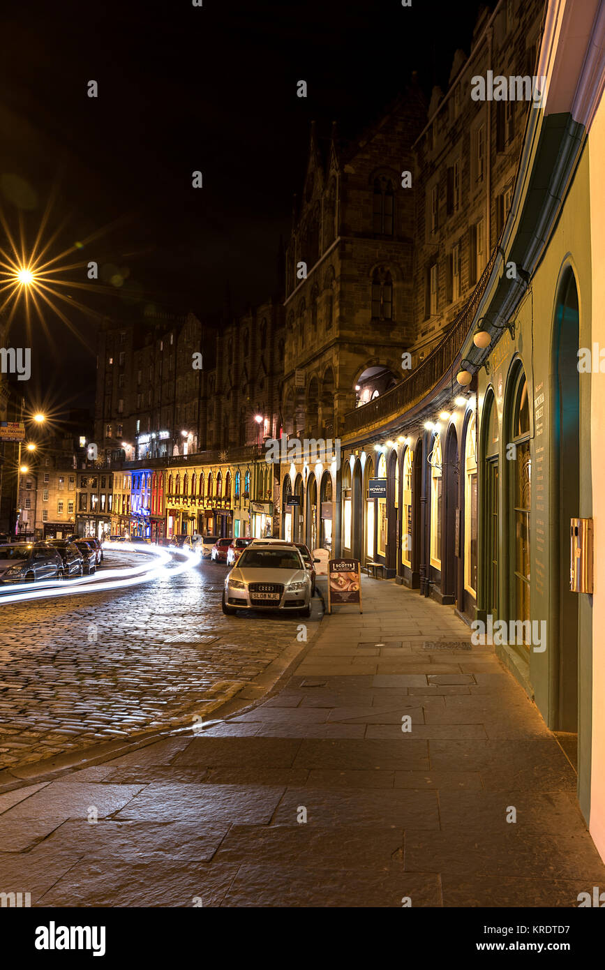 Down hill curved street of Victoria Street, Edinburgh at night with light trails. - Stock Image
