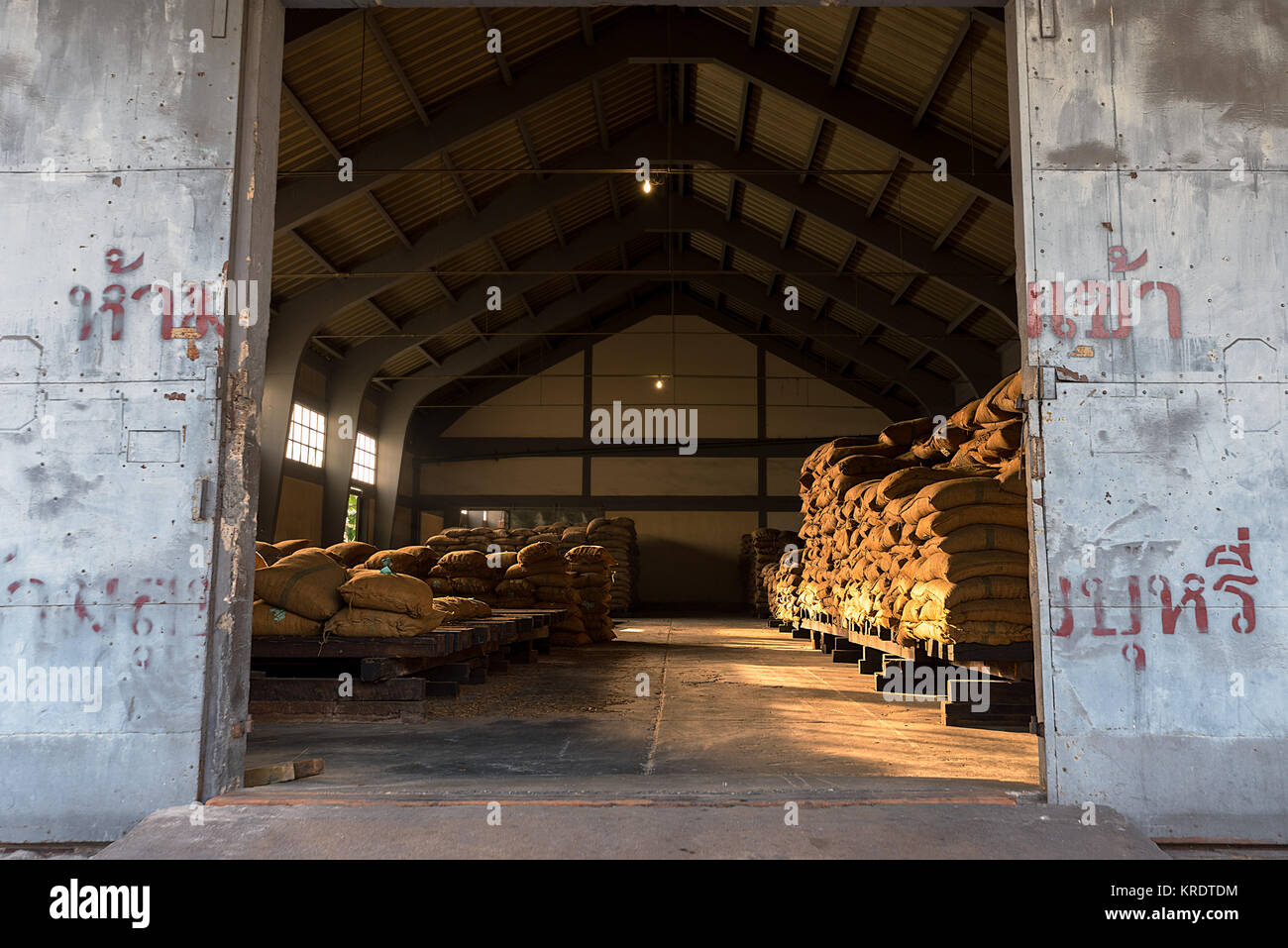 Piled up full hessian sacks awaiting collection in a a large warehouse through an open door. - Stock Image
