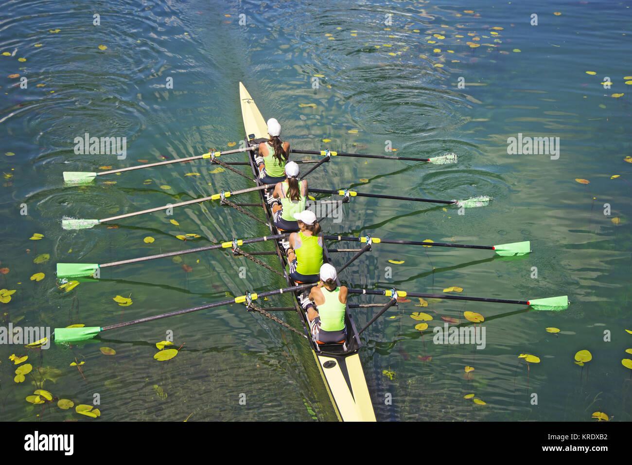 Team of rowing Four-oar women in boat - Stock Image