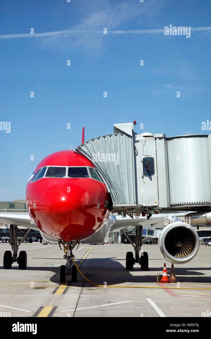 A jet aircraft being refuelled on the runway at a moderm airport with gangway or airbridge or tunnel attached. Taken - Stock Image
