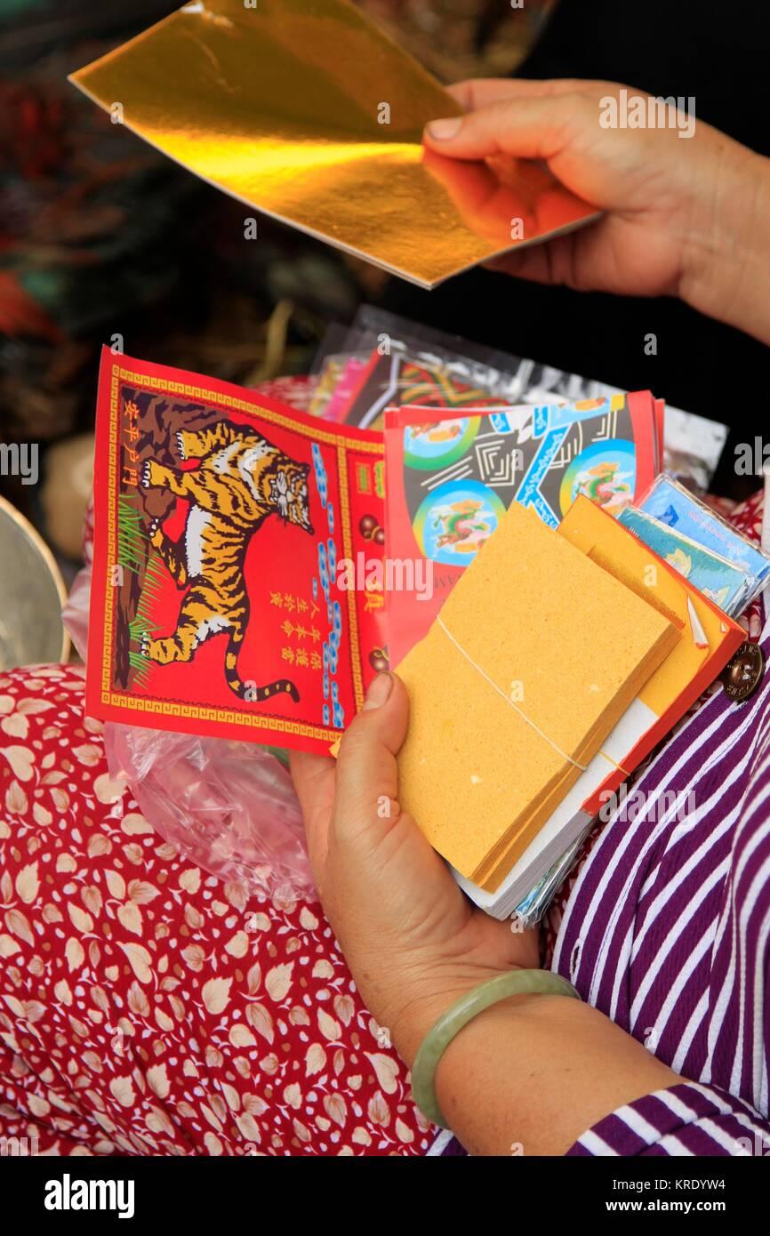 Woman sorting through calendars at a Vietnamese market stall, Mekong Delta - Stock Image