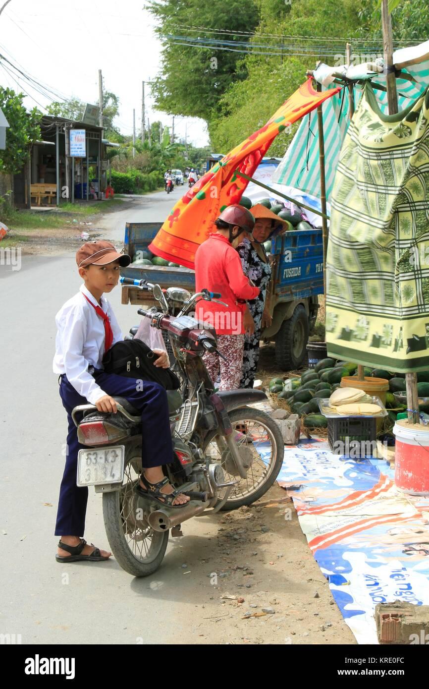 Vietnamese school boy waiting for mother to buy watermelons, Mekong Delta, Vietnam - Stock Image