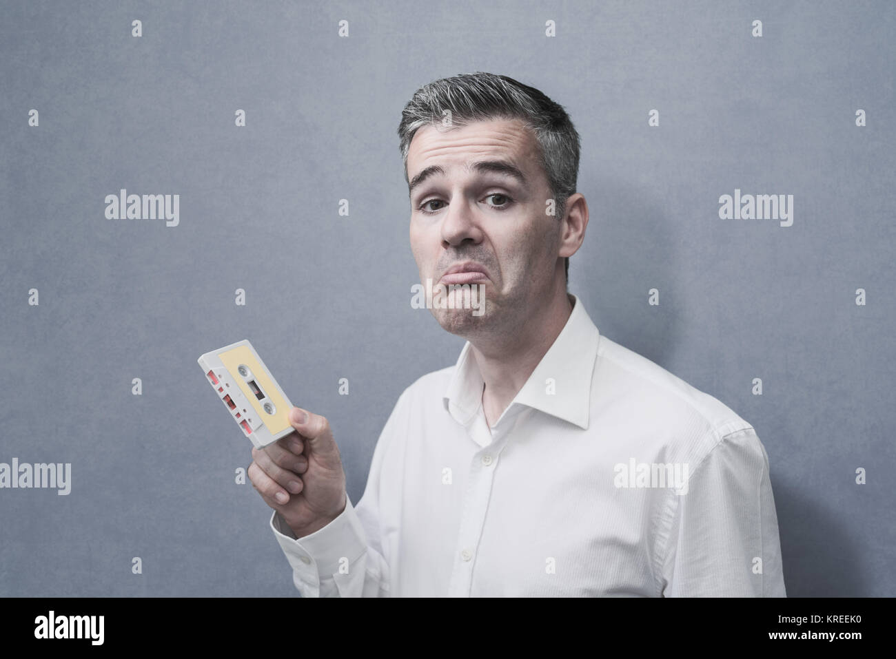 Clueless confused man holding an old audio cassette, vintage outdated technology concept - Stock Image