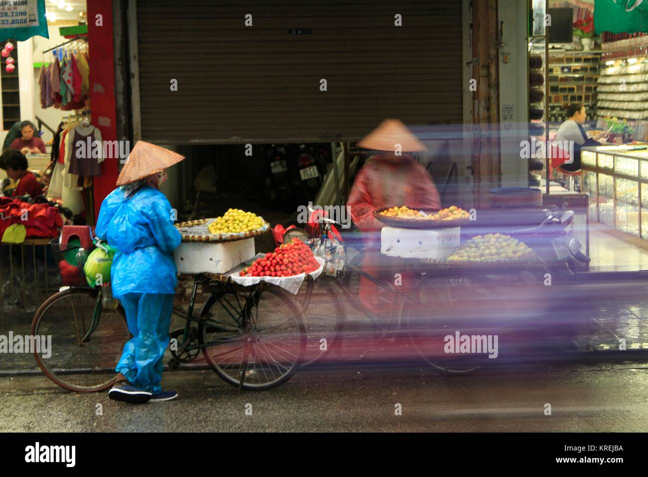Motorbike blur obscuring bike fruit sellers in rain ponchos discussing strategy on a soggy day in the streets of - Stock Image