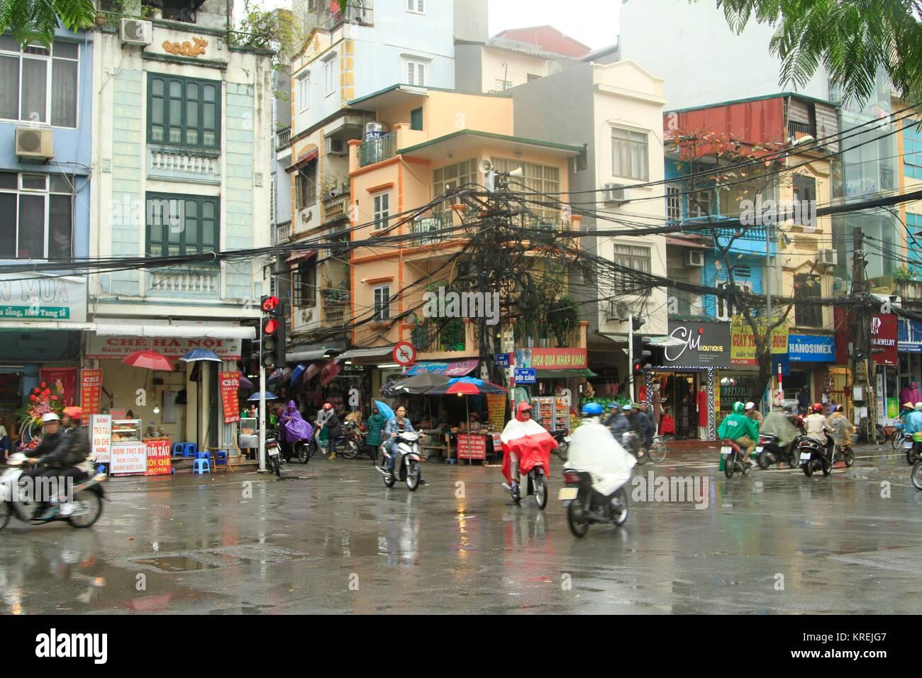 Rainy day street corner displaying the overhead Vietnamese electrical grid, Hanoi, Vietnam - Stock Image