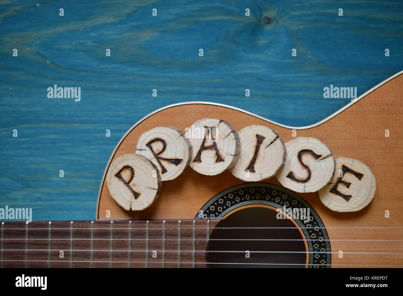 guitar on blue green wood with word: praise - Stock Image