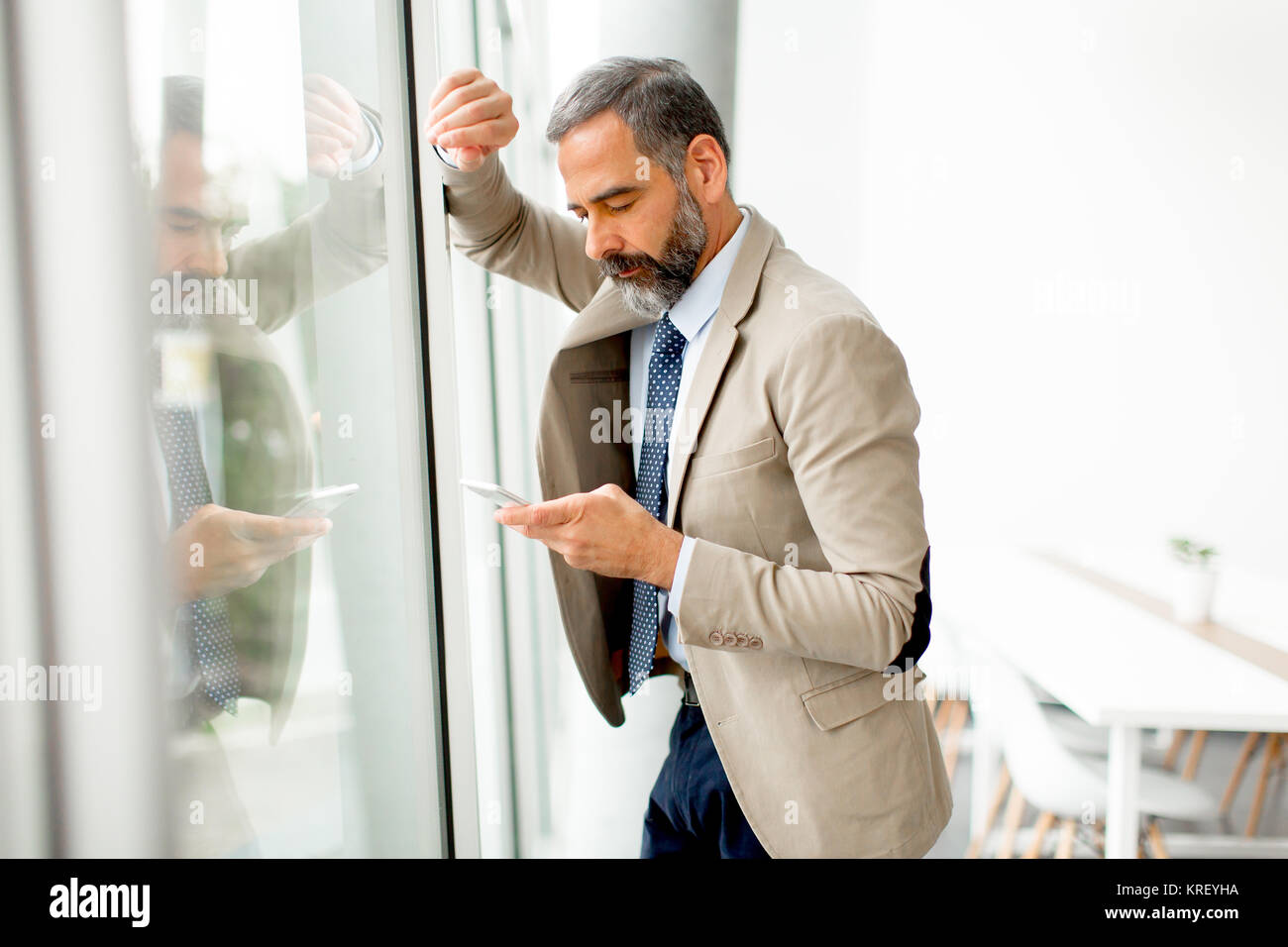 Handsome mature businessman  with mobile phone in the office - Stock Image