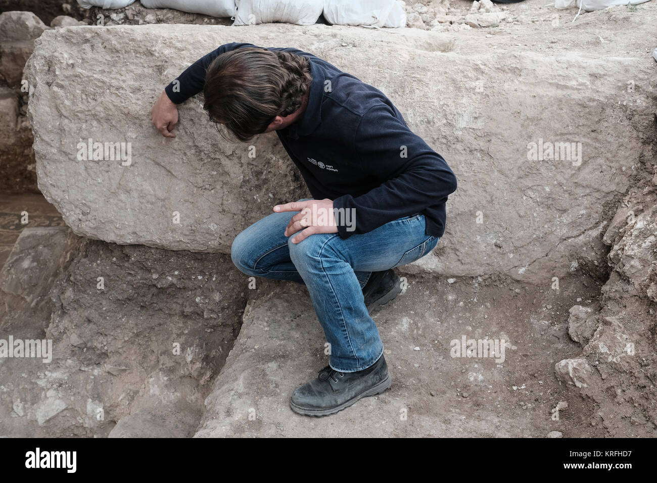 An archaeologist points to the vague engravement of a Maltese Cross on a huge stone which probably served as an - Stock Image