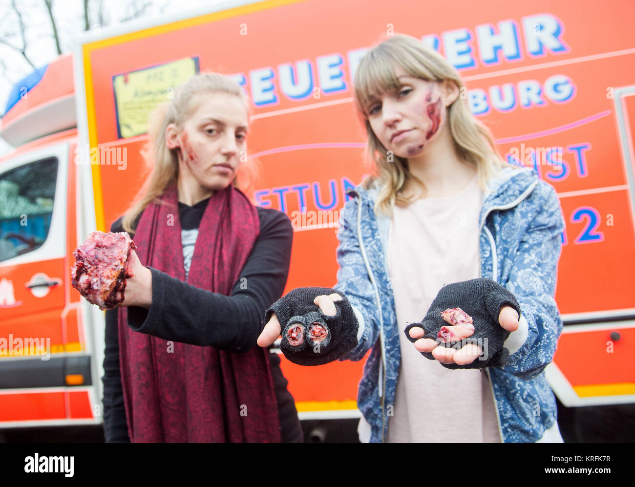 Two young women present fake injuries that could be caused by fireworks during a presentation of the firebrigade - Stock Image