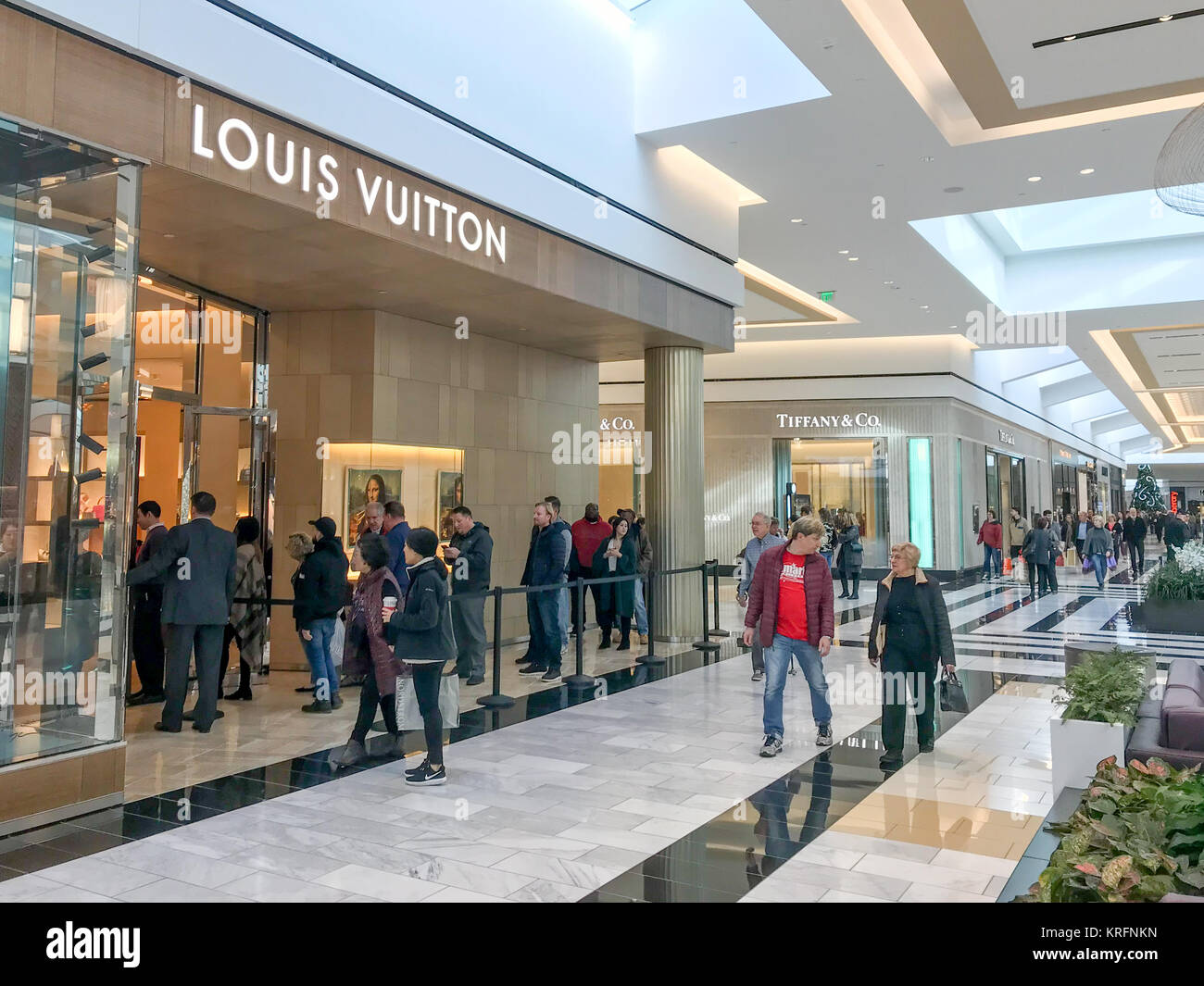 King of Prussia, Pennsylvania, USA. 20th December, 2017. Shoppers wait in line outside of the Louis Vuitton store - Stock Image