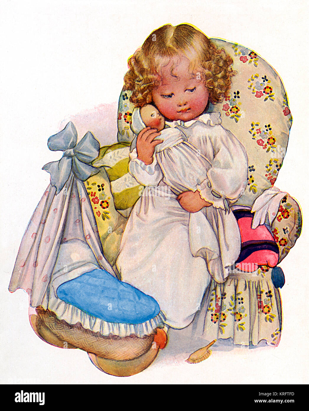 A little girl sits in a comfortable looking floral upholstered armchair and cuddles her baby doll.  A toy cradle - Stock Image