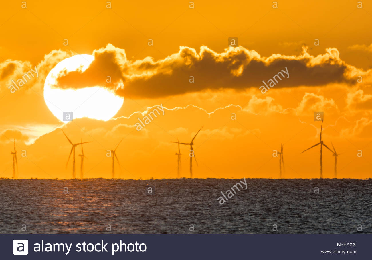 Sun rising over the sea showing the Rampion Wind Farm turbines in the sea off the South Coast of England, UK. - Stock Image