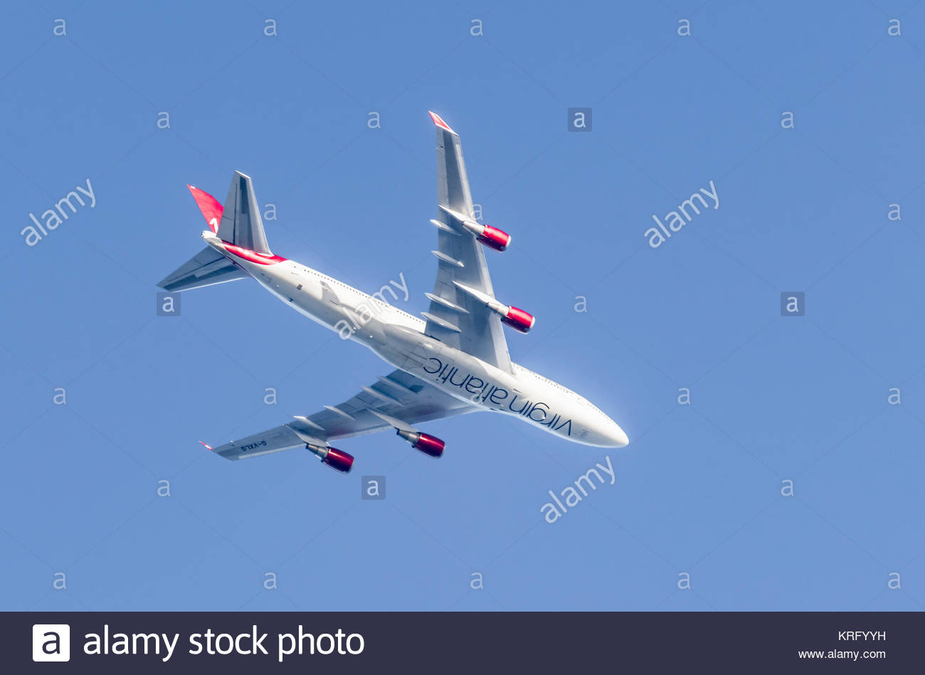 Virgin Atlantic Aeroplane flying high against blue sky in the UK. - Stock Image