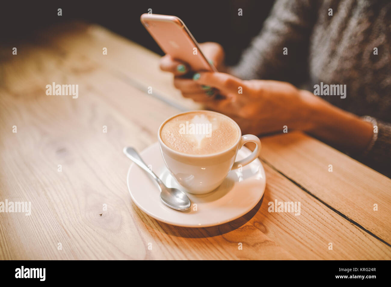 hands close-up of a beautiful young girl uses,types text on a mobile phone at a wooden table near a window and drinks - Stock Image