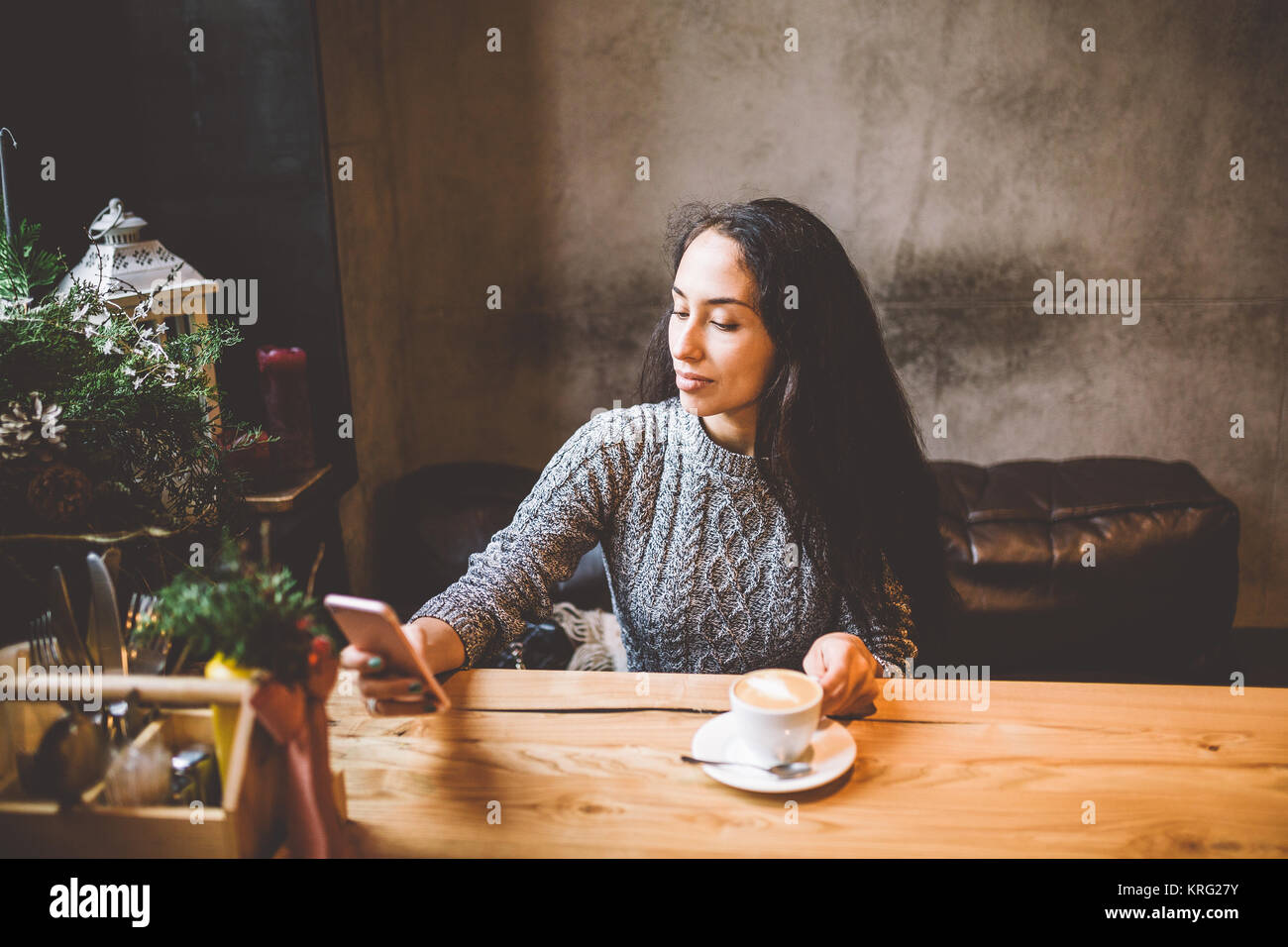 beautiful young girl uses, types text on a mobile phone at a wooden table near the window and drinks coffee in a - Stock Image