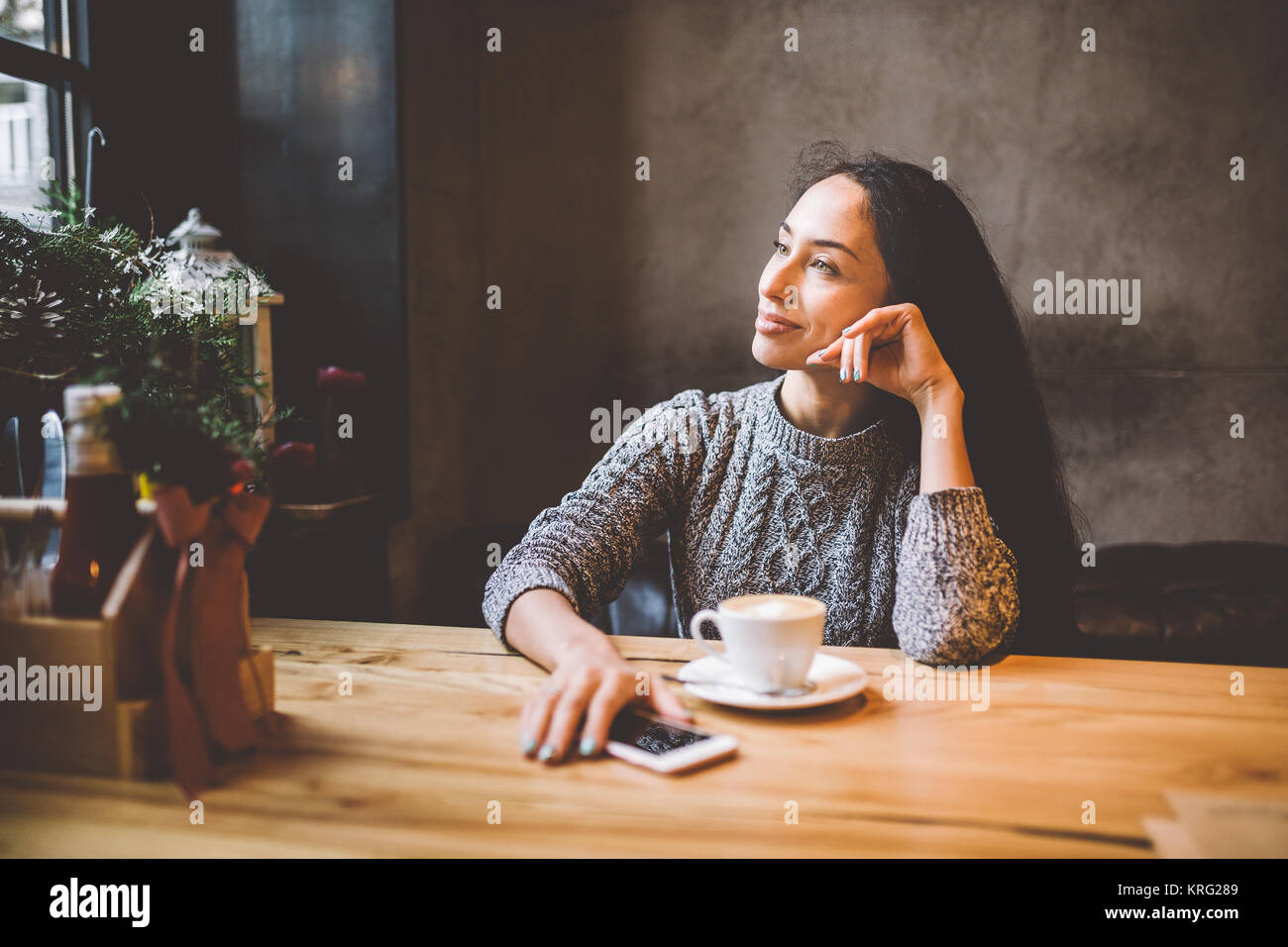 beautiful young girl drinks coffee from a white cup, next to her cell phone in a cafe decorated with Christmas decor. - Stock Image