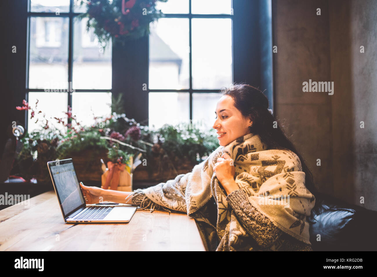beautiful young girl uses laptop technology, types text looking at the monitor in a cafe by the window at wooden - Stock Image