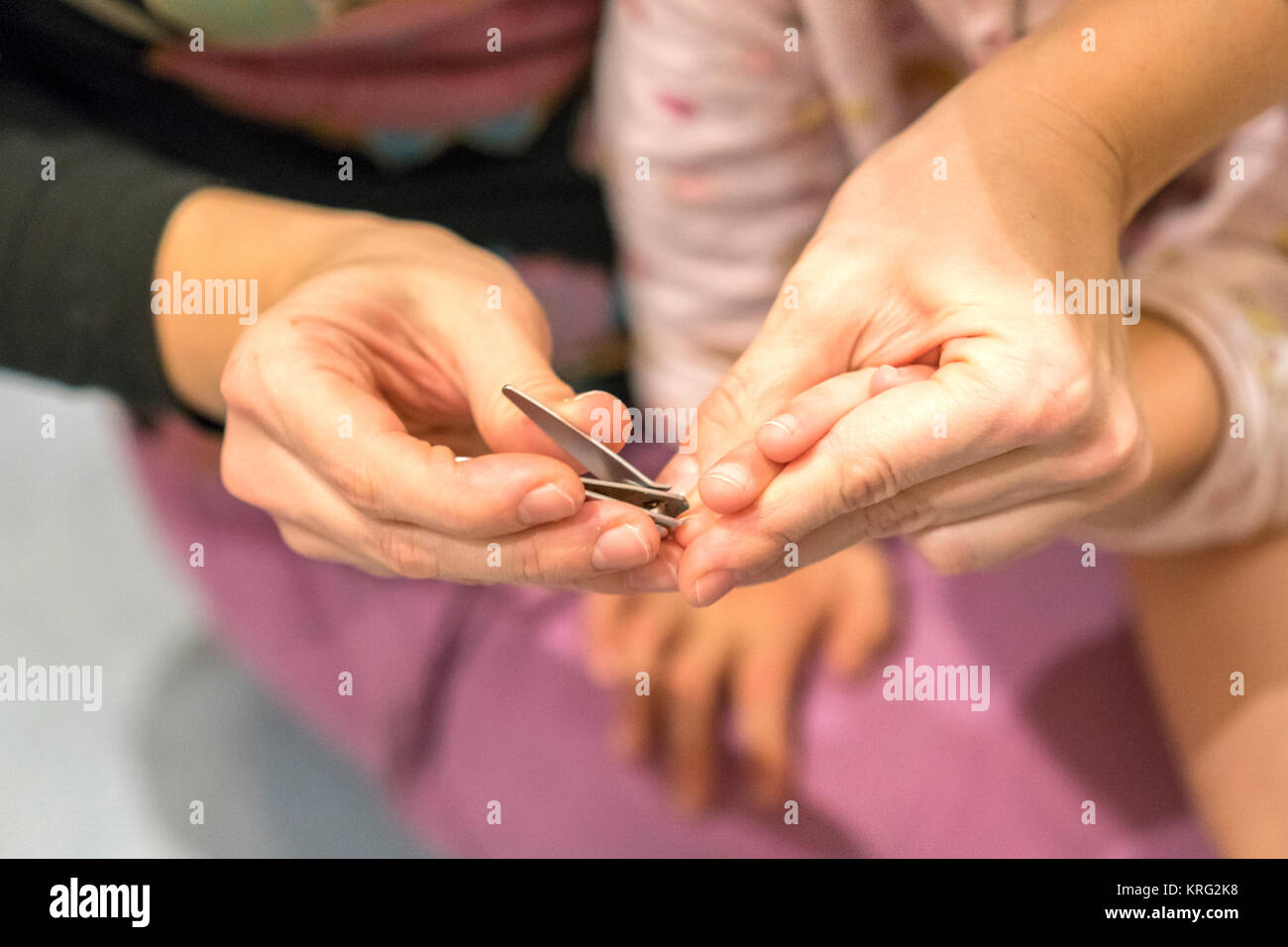 Mom is cutting finger nails to her son, selective focus, background ...