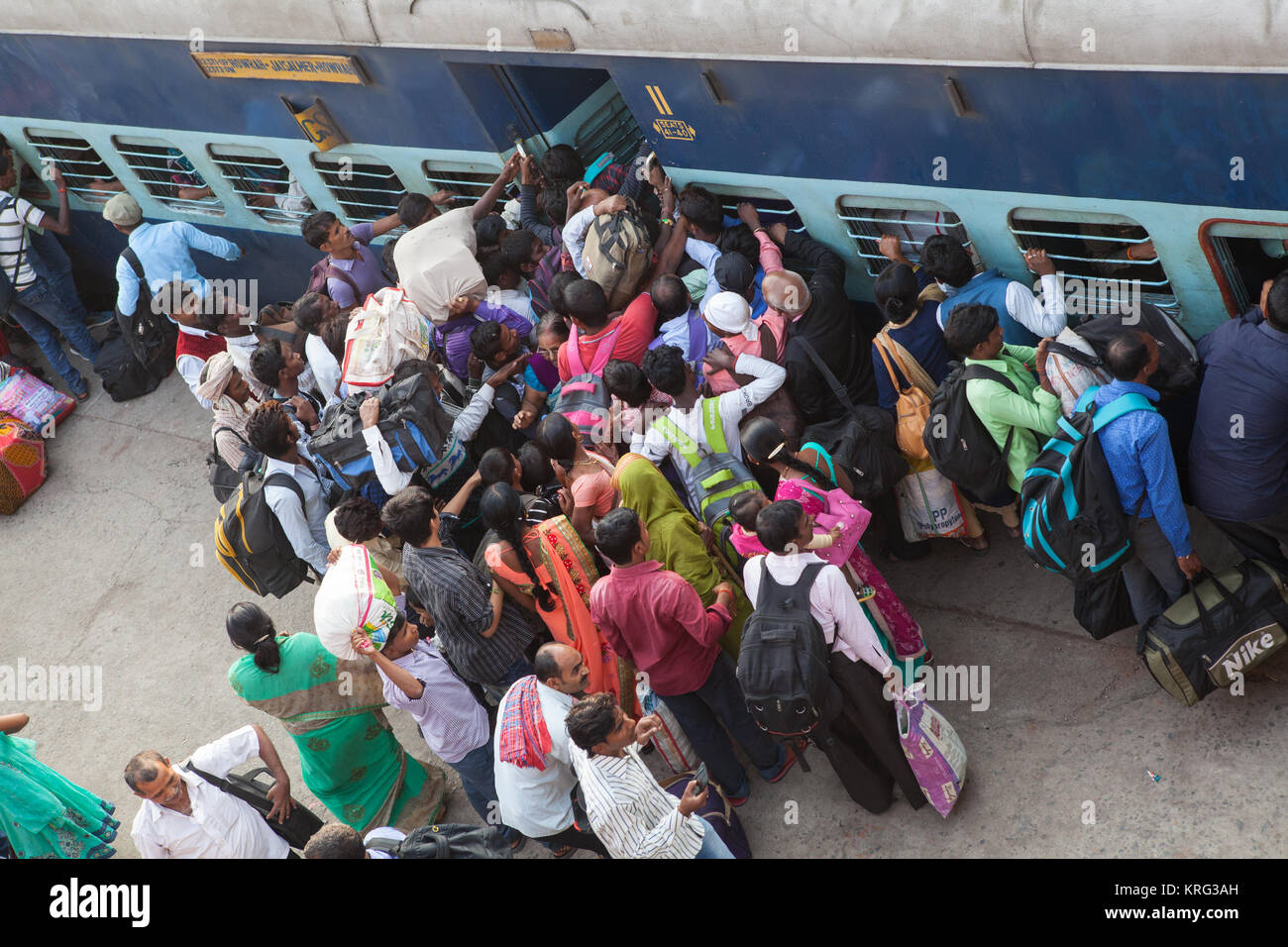 Passengers fight to scramble aboard a train at the railway station in Gaya, India - Stock Image