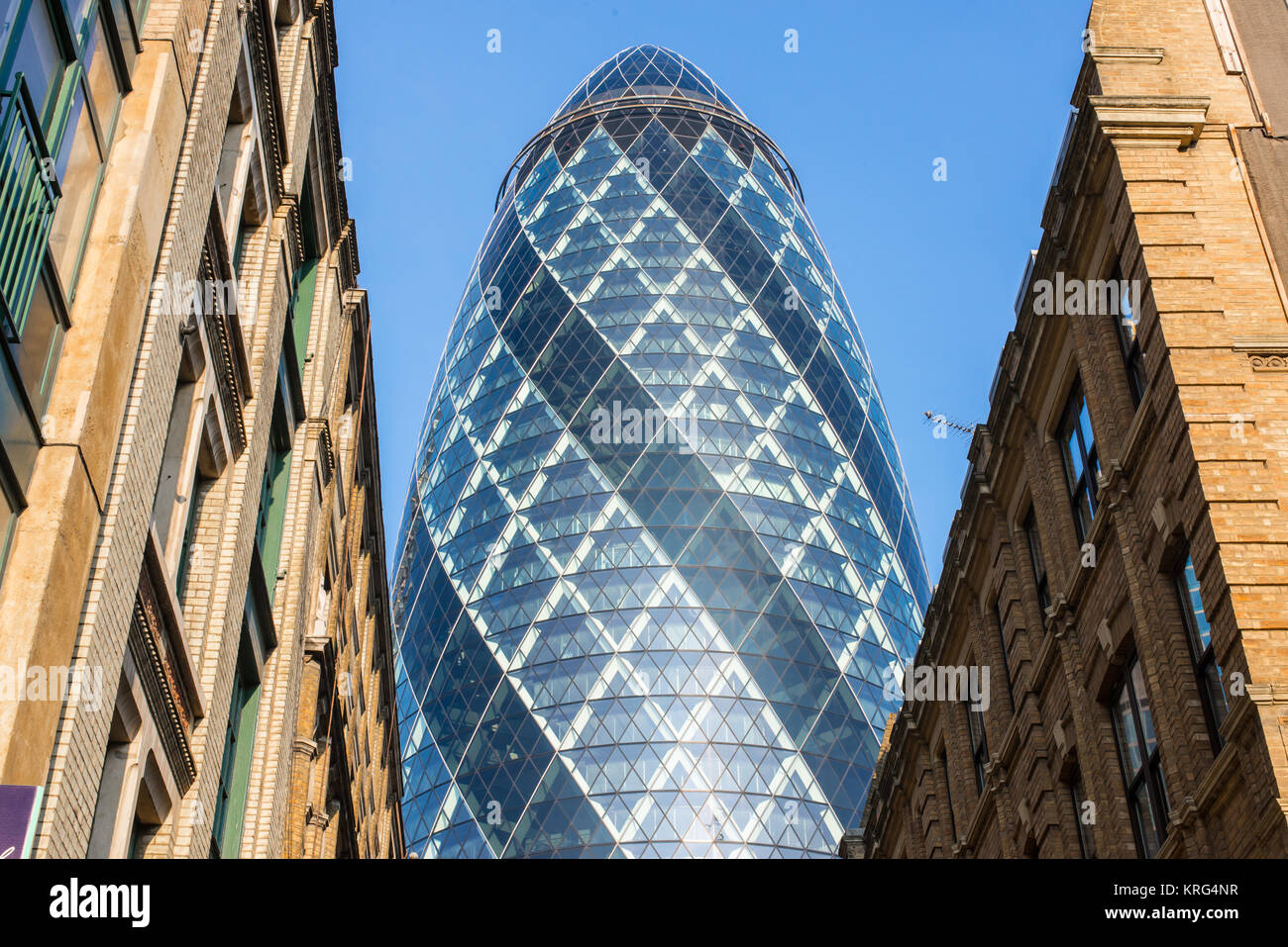 View of the Gherkin, 30 St Mary Axe  skyscraper building from below towering over nearby office buildings. St Mary - Stock Image
