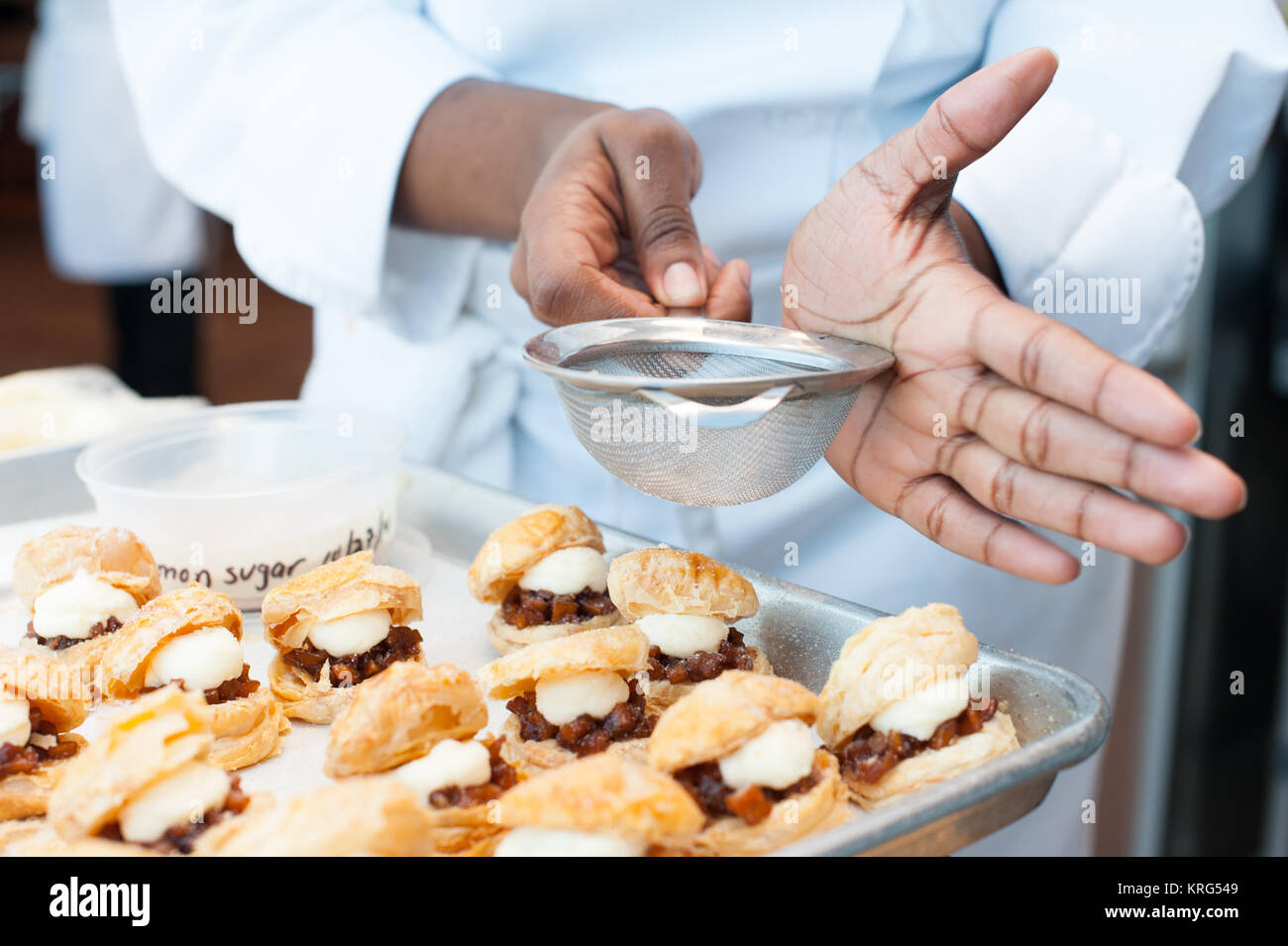 Cream puffs and dried fruit with a sugar sifter - Stock Image