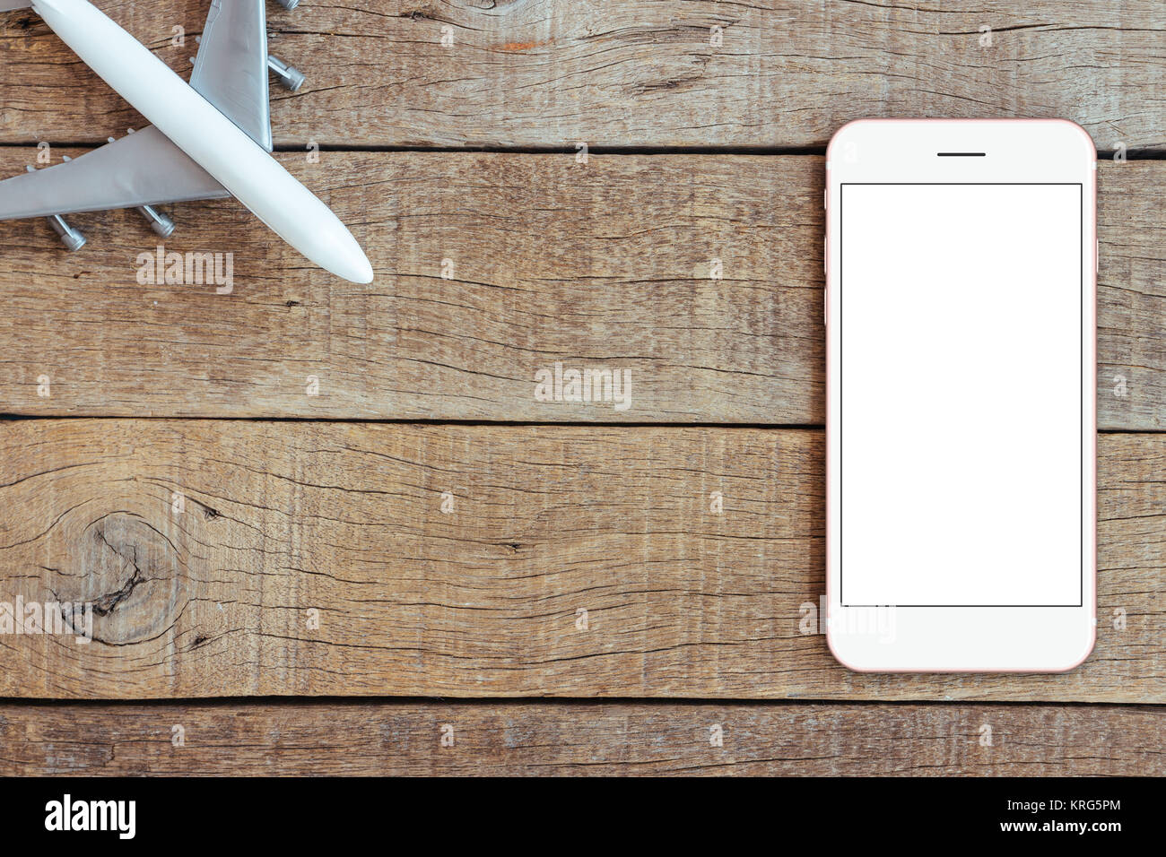 phone and airplane toy on wood table transport business concept top view, mock up phone blank screen - Stock Image
