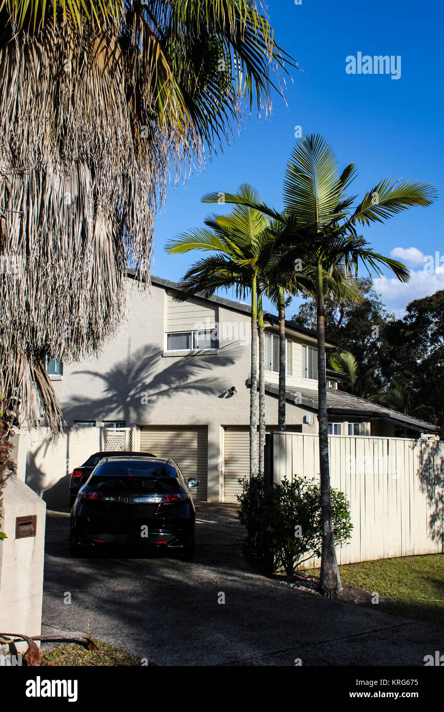 Suburban subtropical house near Brisbane Australia with topical trees dramatic shadows and two cars in the driveway - Stock Image