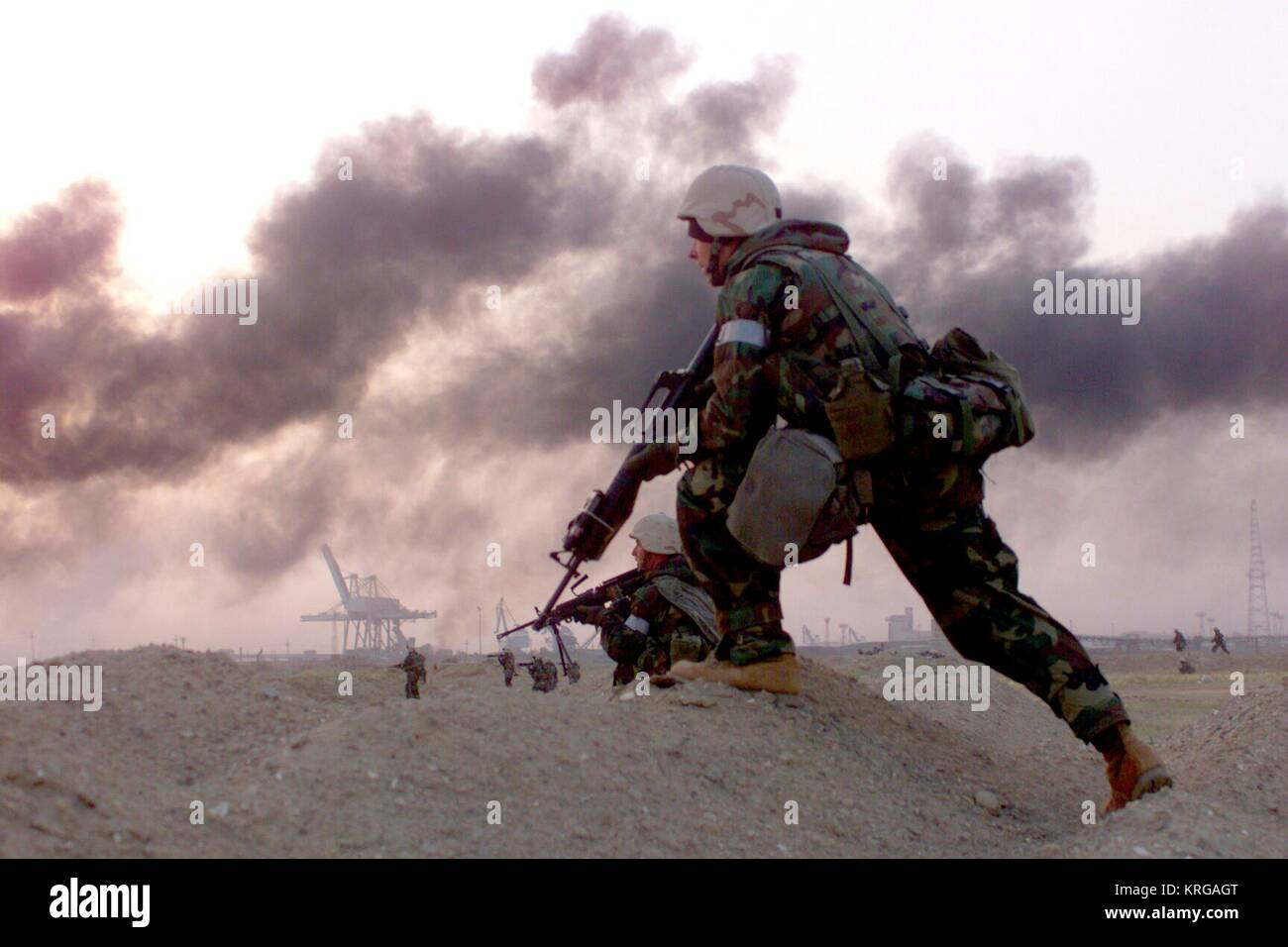 A U.S. Marine soldier sprints over foothills and trenches during Operation Iraqi Freedom March 23, 2003 in Az Zubayr, - Stock Image
