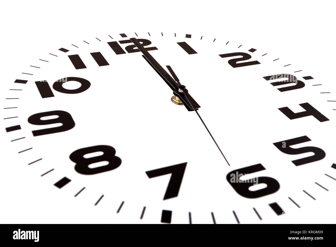 Clock isolated on white marking the twelve o'clock hour. The main focus is in the hour hand. - Stock Image