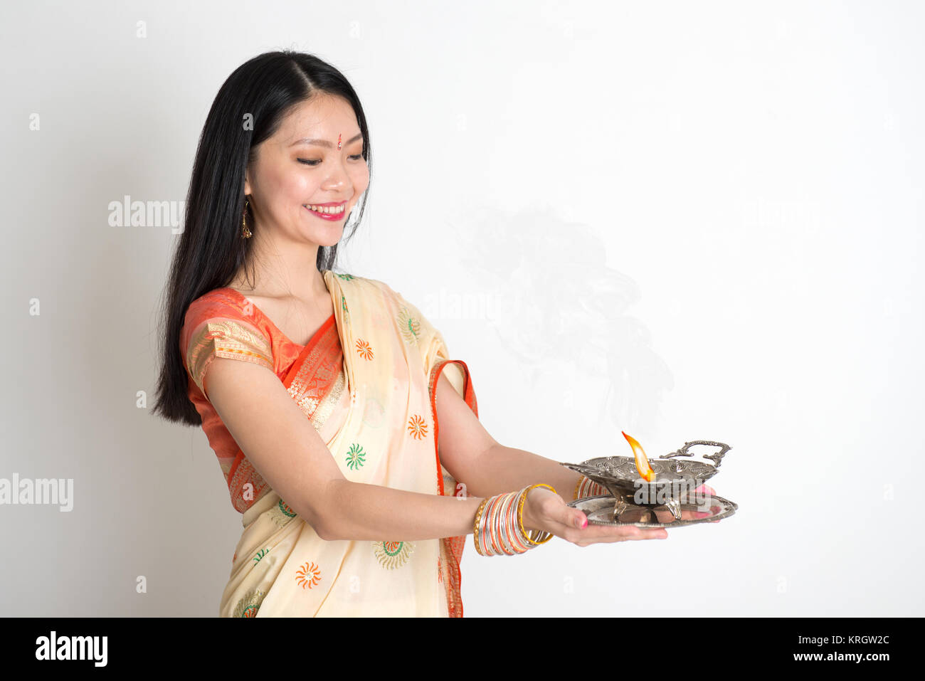 Female with Indian sari dress holding oil lamp - Stock Image