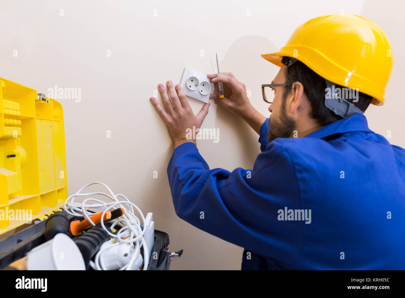 electrician installing wall socket - Stock Image