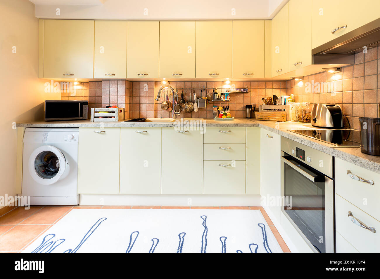 A modern kitchen with laminated cupboards and cabinets, washing machine, cooker, microwave and kitchenware. - Stock Image