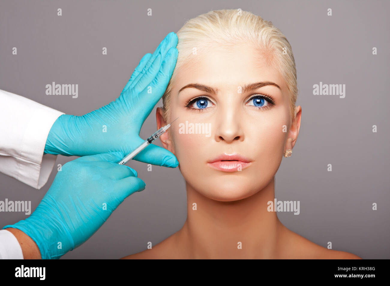 Cosmetic plastic surgeon injecting aesthetics face - Stock Image