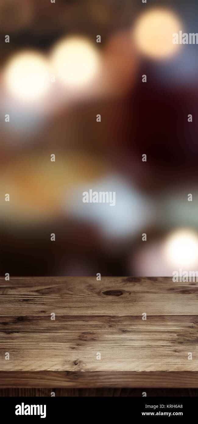 Abstract background with colored light dots in front of an empty wooden table for a concept Stock Photo