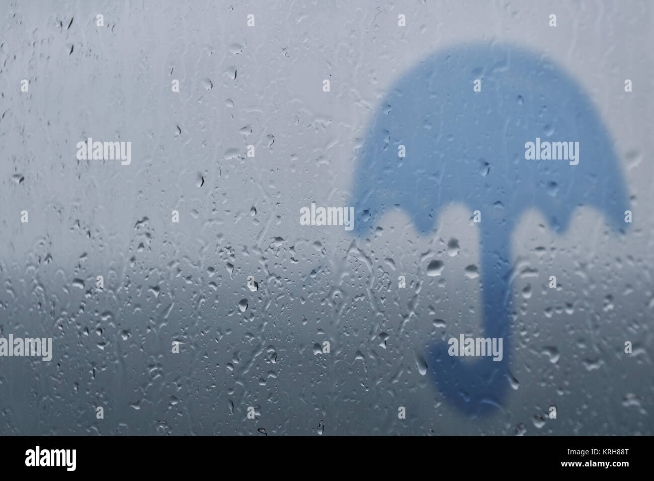 Silhouette of an umbrella on a background of glass with drops and raindrops. Autumn rain. - Stock Image
