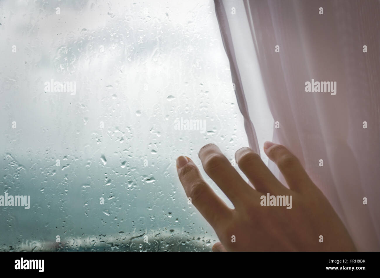 Rainy weather - a woman's hand pulls the blind from the rainy window. - Stock Image