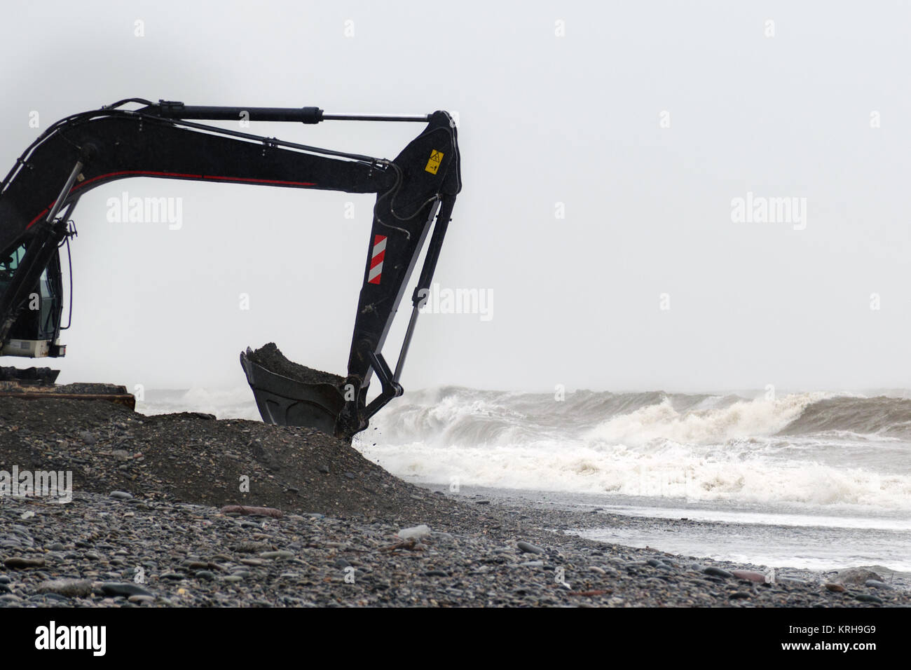 The excavator works with a bucket full of stones on the seashore in stormy weather. - Stock Image