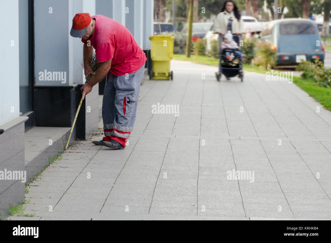 A city cleaner collects garbage near a building near the sidewalk. - Stock Image
