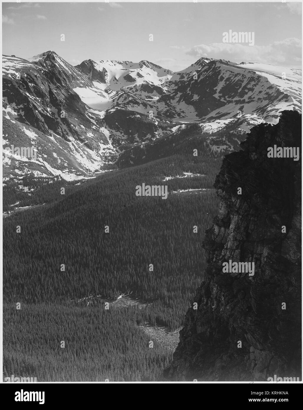 View of snow-capped mountain timbered area below 'In Rocky Mountain National Park' Colorado. (Vertical Orientation) - Stock Image