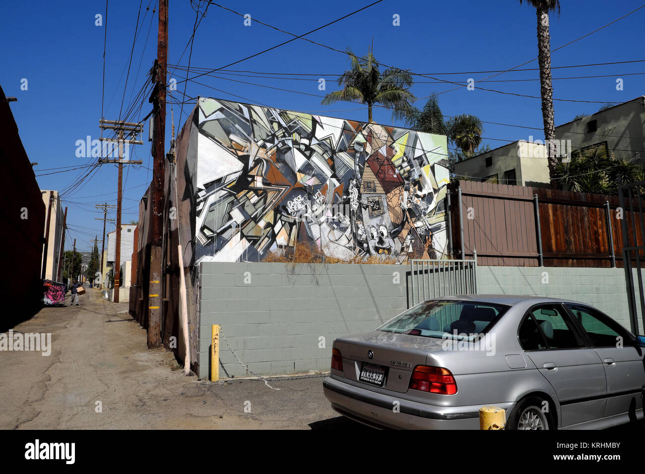 An abstract mural on a wall and parked car in a back alley in the Los Feliz neighbourhood of Los Angeles, California - Stock Image